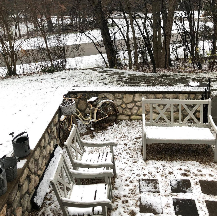 Light snowfall in our French inspired courtyard in Northern Illinois with rustic river rock stone walls - Hello Lovely Studio.